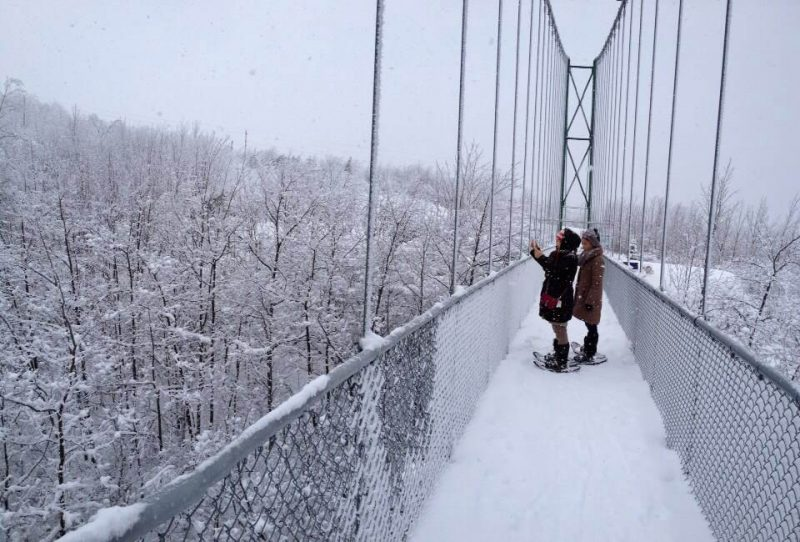 Snowshoeing across the suspension bridge at the Scenic Caves Nordic Centre - Winter hiking